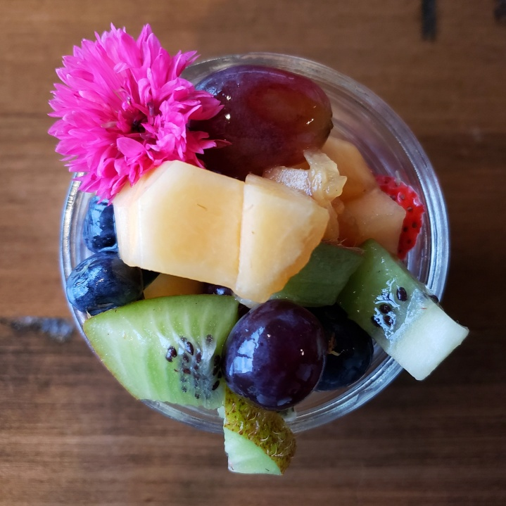 Mason jar of seasonal fresh fruit (kiwi, strawberry, blueberries, blackberries, grapes, and melon), at Fahrenheit Charlotte brunch in North Carolina