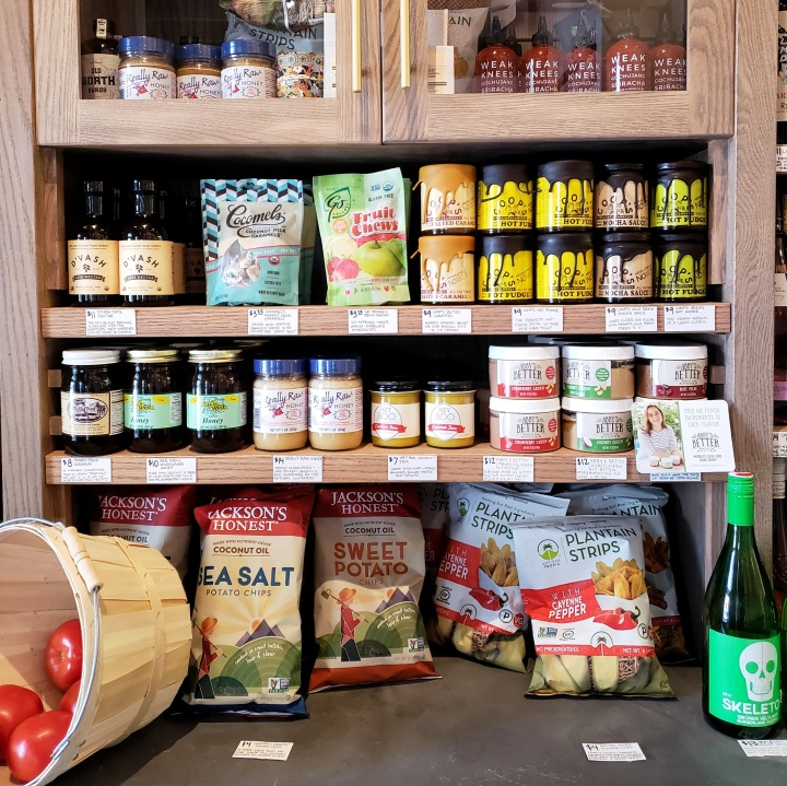 Goods available for purchase in the market, including chips, raw honey, caramels, and date nectar