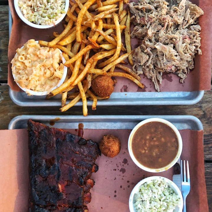 The Pig Plate with Mac + Cheese and Fries and the Ribs Plate with beans and hushpuppies from Sauceman's